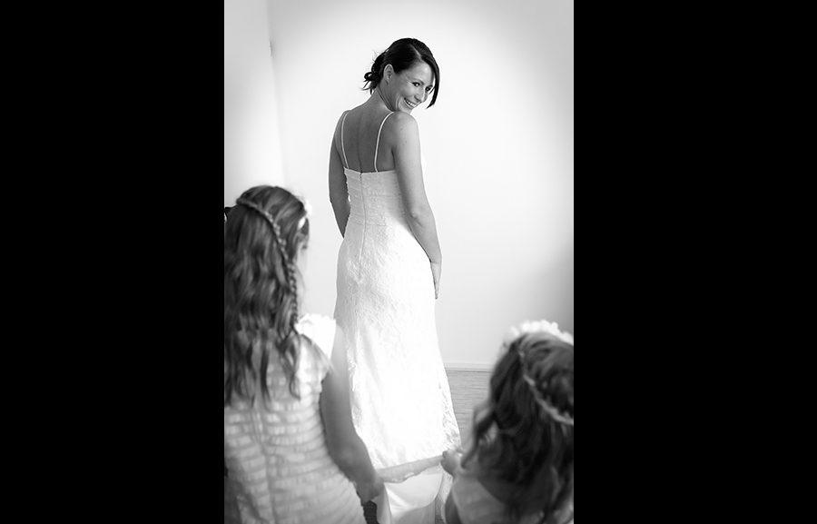 De bruidsmeisjes kijken goedkeurend naar de mooie jurk
