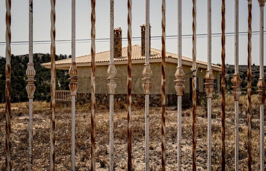 een losstaand, verroest hek voor een kleine villa, die ook weer onbewoond is